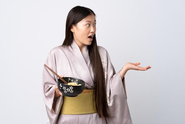 Junges chinesisches mädchen, das kimono isoliert trägt