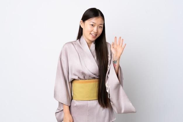 Junges chinesisches mädchen, das kimono trägt, der mit hand mit glücklichem ausdruck salutiert