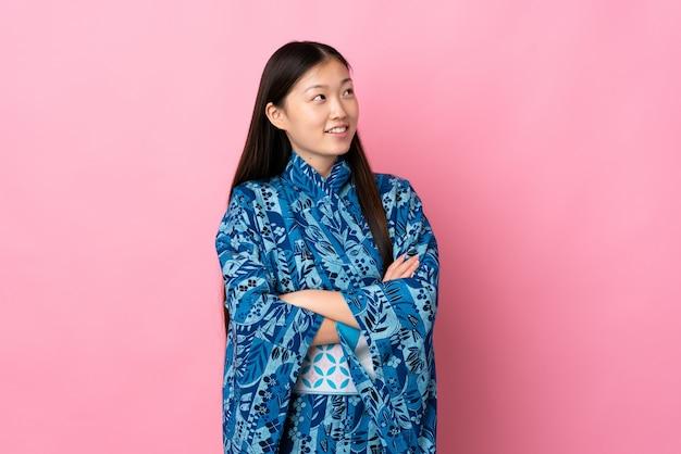 Junges chinesisches mädchen, das kimono trägt, der oben beim lächeln schaut