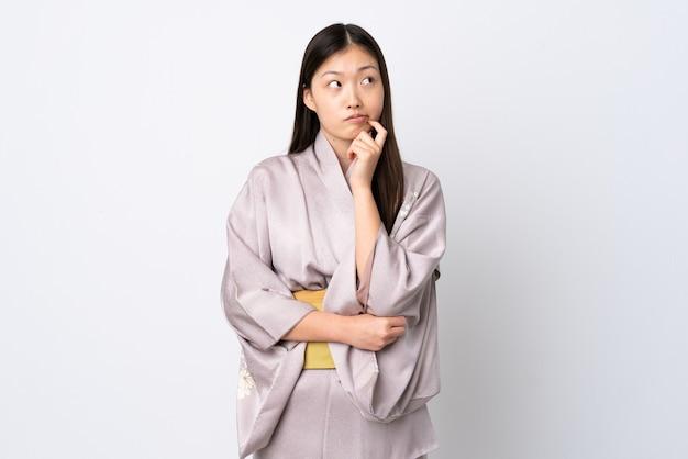 Junges chinesisches mädchen, das kimono trägt, der zweifel hat und denkt