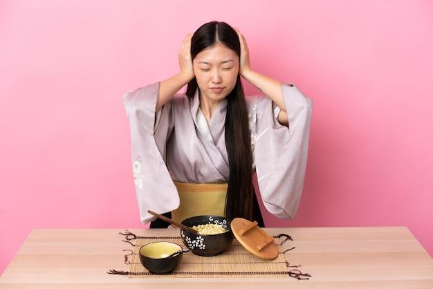 Junges chinesisches mädchen, das kimono trägt und frustrierte nudeln isst und ohren kegelt