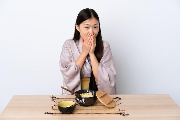 Junges chinesisches mädchen, das kimono trägt und nudeln glücklich und lächelnd bedeckt mund mit händen isst