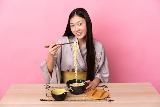 Junges chinesisches mädchen, das kimono trägt und nudeln in einer tabelle über rosa hintergrund isst