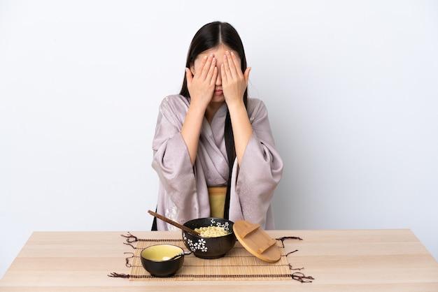 Junges chinesisches mädchen, das kimono trägt und nudeln isst, die augen durch hände bedecken