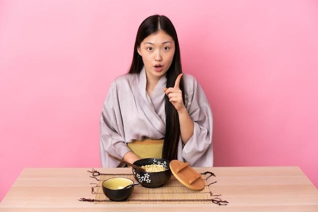 Junges chinesisches mädchen, das kimono trägt und nudeln isst, die beabsichtigen, die lösung zu realisieren, während sie einen finger anheben