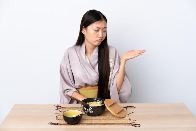 Junges chinesisches mädchen, das kimono trägt und nudeln isst, die copyspace mit zweifeln halten