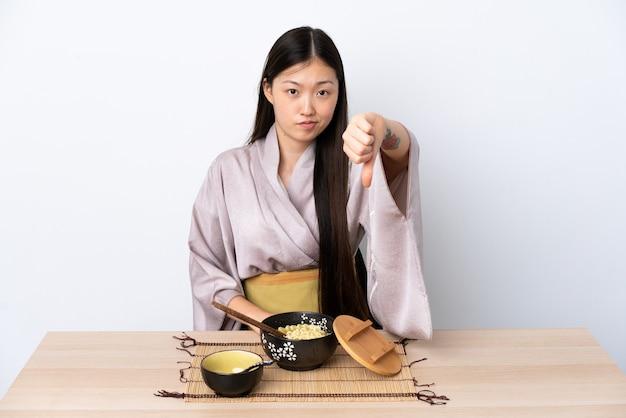 Junges chinesisches mädchen, das kimono trägt und nudeln isst, die daumen nach unten zeigen