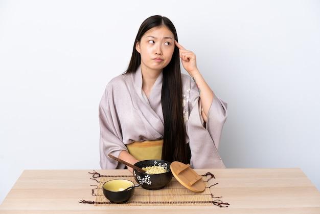 Junges chinesisches mädchen, das kimono trägt und nudeln isst, die die geste des wahnsinns machen