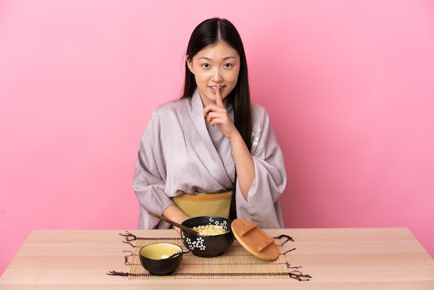 Junges chinesisches mädchen, das kimono trägt und nudeln isst, die ein zeichen der stille geste zeigen, die finger in den mund setzt