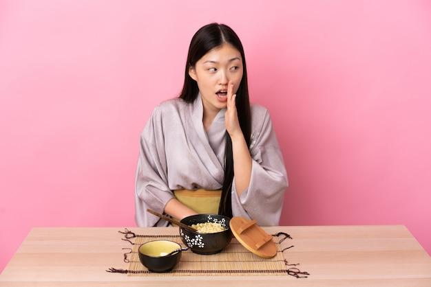 Junges chinesisches mädchen, das kimono trägt und nudeln isst, die etwas mit überraschungsgeste flüstern, während sie zur seite schauen