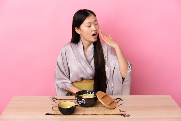 Junges chinesisches mädchen, das kimono trägt und nudeln isst, die gähnen und weit geöffneten mund mit hand bedecken