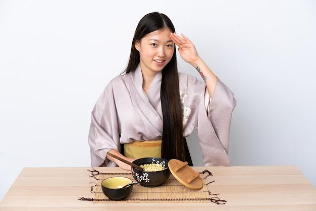 Junges chinesisches mädchen, das kimono trägt und nudeln isst, die mit hand mit glücklichem ausdruck salutieren