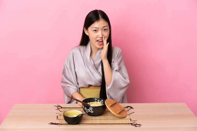 Junges chinesisches mädchen, das kimono trägt und nudeln isst, die mit offenem mund schreien
