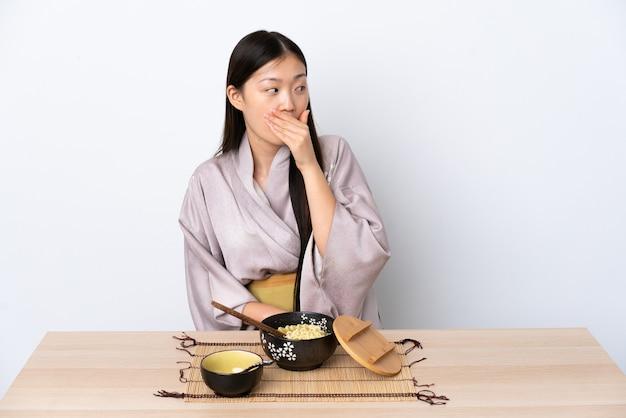 Junges chinesisches mädchen, das kimono trägt und nudeln isst, die überraschungsgeste tun, während sie zur seite schauen