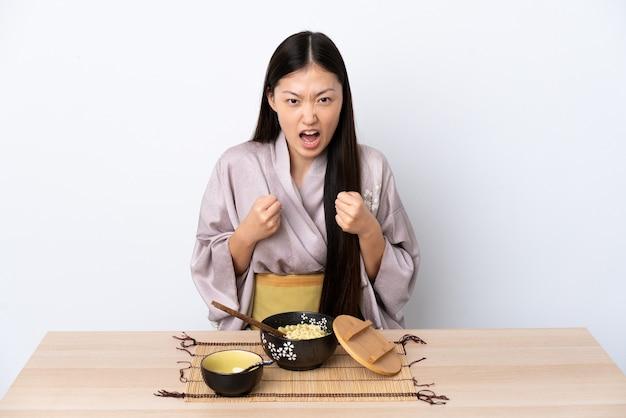 Junges chinesisches mädchen, das kimono trägt und nudeln isst, frustriert von einer schlechten situation