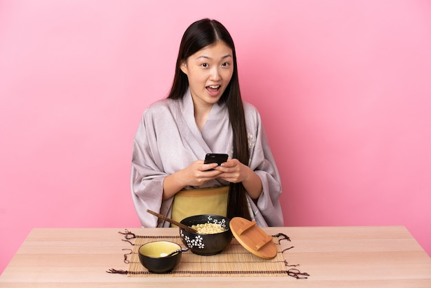 Junges chinesisches mädchen, das kimono trägt und nudeln isst, überrascht und sendet eine nachricht