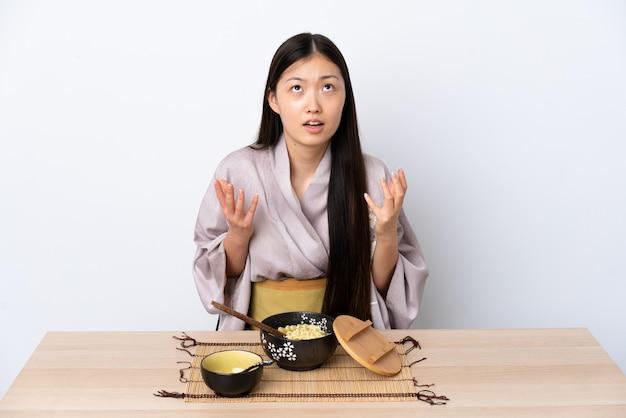 Junges chinesisches mädchen, das kimono trägt und nudeln isst, überwältigt überwältigt