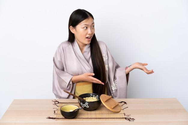 Junges chinesisches mädchen, das kimono trägt und nudeln mit überraschungsausdruck isst, während seite schaut