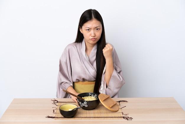 Junges chinesisches mädchen, das kimono trägt und nudeln mit unglücklichem ausdruck isst