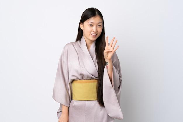 Junges chinesisches mädchen, das kimono über lokalisiertem hintergrund glücklich trägt und vier mit den fingern zählt