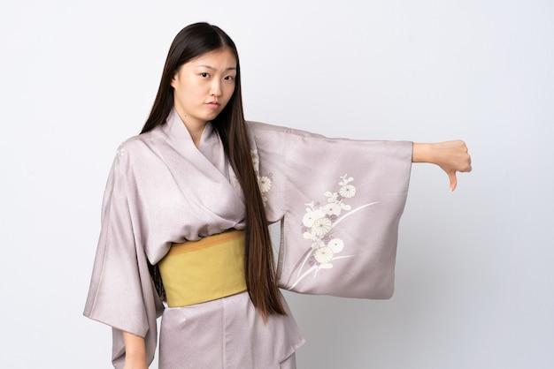 Junges chinesisches mädchen, das kimono über lokalisiertem hintergrund trägt, zeigt daumen unten mit negativem ausdruck
