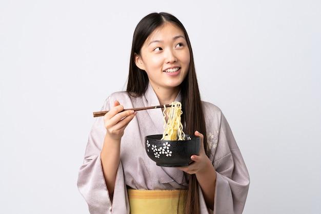 Junges chinesisches mädchen, das kimono über weiß hält, der eine schüssel nudeln mit stäbchen hält und nach oben schaut