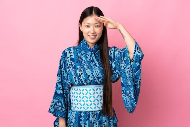 Junges chinesisches mädchen mit kimono über isoliertem hintergrund, das mit der hand mit glücklichem ausdruck grüßt