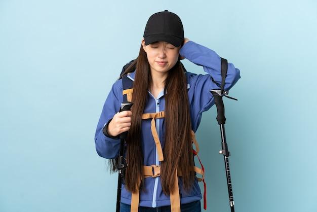 Junges chinesisches mädchen mit rucksack und wanderstöcken isoliert
