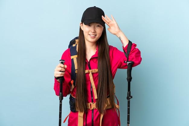 Junges chinesisches mädchen mit rucksack und wanderstöcken über blauem gruß mit hand mit glücklichem ausdruck