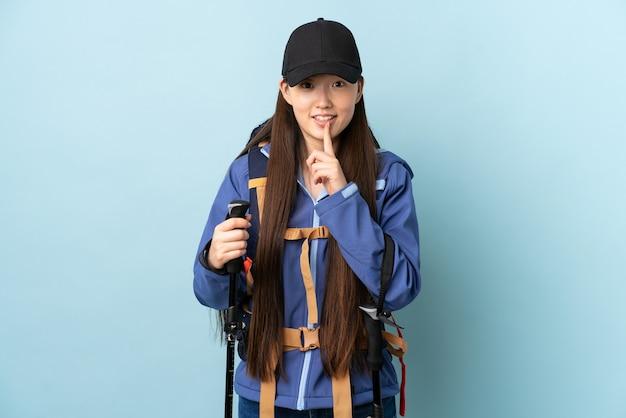 Junges chinesisches mädchen mit rucksack und wanderstöcken über isoliertem blau, das ein zeichen der stille geste zeigt finger in den mund setzt