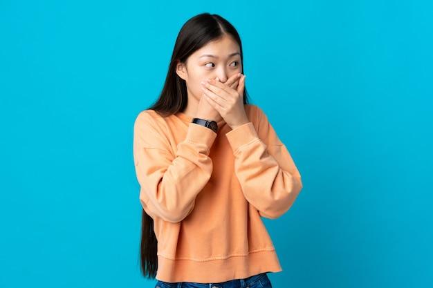 Junges chinesisches mädchen über blau bedeckendem mund und blick zur seite