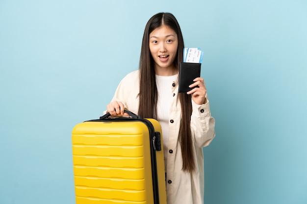Junges chinesisches mädchen über im urlaub mit koffer und pass