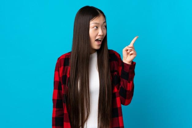 Junges chinesisches mädchen über isoliertem blauem hintergrund, der beabsichtigt, die lösung zu realisieren, während ein finger anhebt