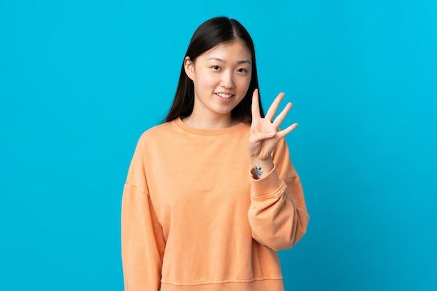 Junges chinesisches mädchen über isoliertem blauem hintergrund glücklich und zählt vier mit den fingern
