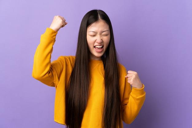 Junges chinesisches mädchen über isoliertem purpur, das einen sieg feiert