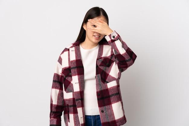 Junges chinesisches mädchen über isolierten weißen bedeckungsaugen durch hände und lächeln