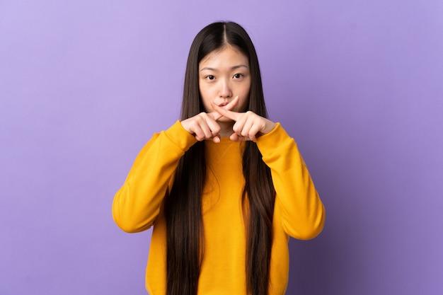 Junges chinesisches mädchen über isolierter lila wand, die ein zeichen der stille geste zeigt