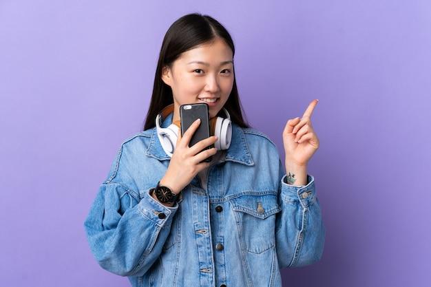 Junges chinesisches mädchen über isolierter lila wand, die musik mit einem handy und gesang hört