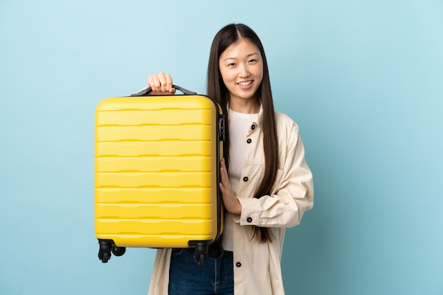 Junges chinesisches mädchen über isolierter wand im urlaub mit reisekoffer