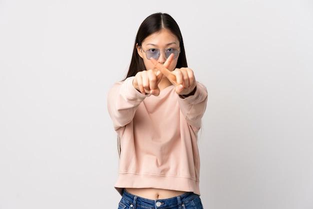 Junges chinesisches mädchen über isolierter weißer wand, die stoppgeste mit ihrer hand macht, um eine handlung zu stoppen