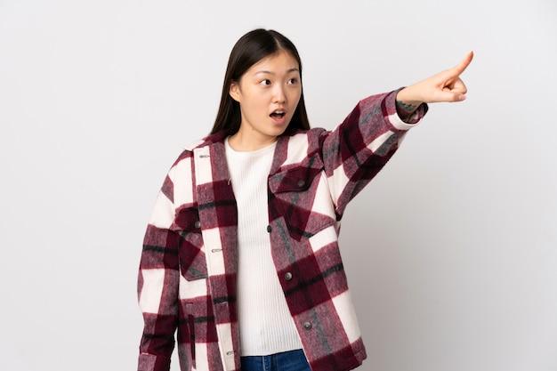 Junges chinesisches mädchen über isolierter weißer wand, die weg zeigt