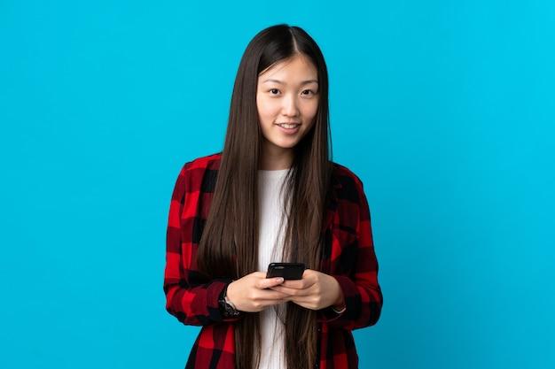 Junges chinesisches mädchen über lokalisiertem blauem hintergrund, das eine nachricht mit dem handy sendet