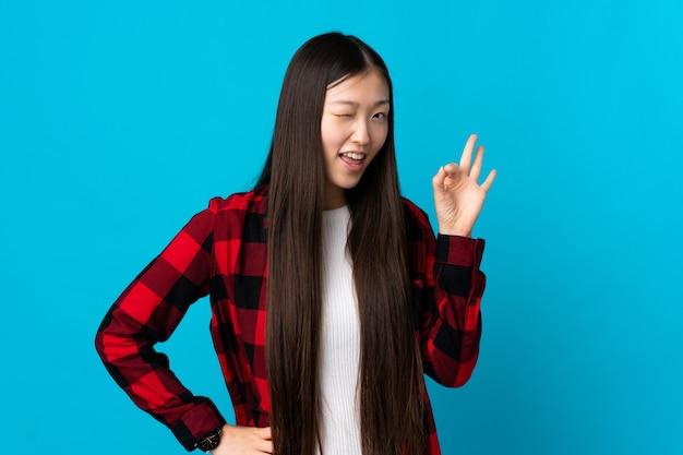 Junges chinesisches mädchen über lokalisiertem blauem hintergrund, der ok zeichen mit den fingern zeigt