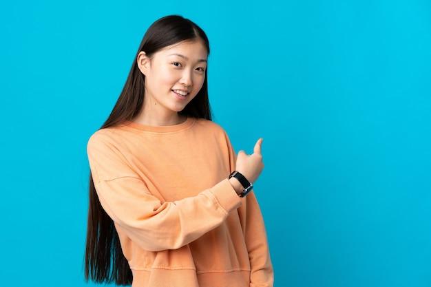 Junges chinesisches mädchen über lokalisiertem blauem hintergrund, der zurück zeigt