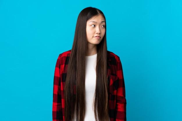Junges chinesisches mädchen über lokalisiertem blauem hintergrund, der zweifel macht, die seite schauen