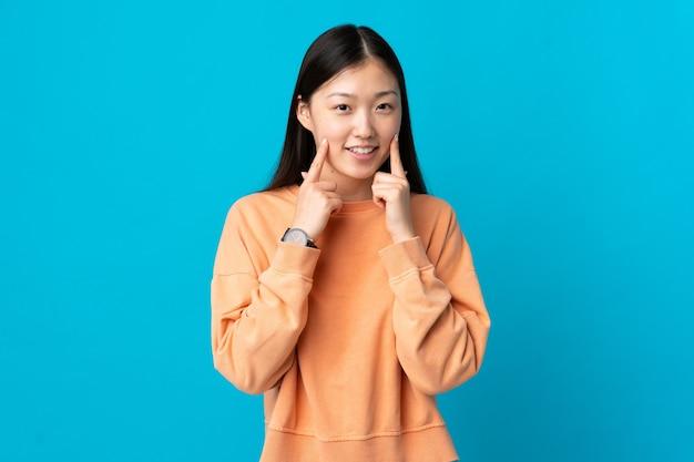 Junges chinesisches mädchen über lokalisiertem blauem hintergrund lächelnd mit einem glücklichen und angenehmen ausdruck