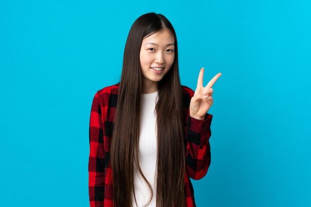 Junges chinesisches mädchen über lokalisiertem blauem hintergrund lächelnd und siegeszeichen zeigend