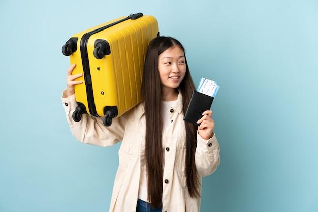 Junges chinesisches mädchen über wand im urlaub mit koffer und pass