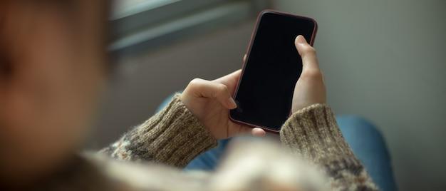 Junges college-mädchen, das entspannt auf stuhl im wohnzimmer liegt und smartphone verwendet
