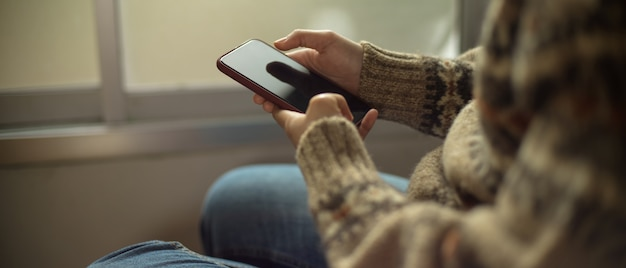 Junges college-mädchen, das smartphone beim sitzen auf stuhl neben fenster verwendet